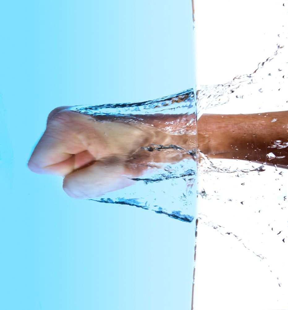 Fist beating into Water, vertical, splash